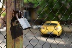 Automobile gialla dietro il recinto della grata Immagine Stock