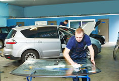 Automobile glazier cleaning car windscreen or windshield in service garage Stock Photos