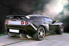 Automobile isolata del nero di sport sulla priorità bassa del cielo blu Fotografie Stock