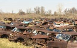 An automobile junk yard in a rural area. Abandoned automobiles in a field in a rural area rusting away stock photos