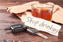 Automobile keys, message, glass of alcohol. Message stop drinking, car keys, glass of alcohol beverage. Stop drinking and obey the law stock images