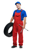 Automobile mechanic with car tire and spanner. Serviceman repairman automobile mechanic with car tire and spanner wrench isolated royalty free stock photography