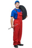 Automobile mechanic with car tire and spanner. Serviceman repairman automobile mechanic with car tire and spanner wrench isolated royalty free stock images