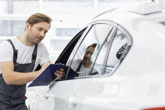 Automobile mechanic writing on clipboard while examining car in repair shop Royalty Free Stock Image