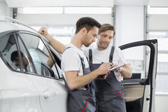 Automobile mechanics checking checklist while standing by car in workshop Stock Images