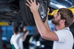 Automobile mechanics repairing a car Royalty Free Stock Photography