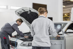 Automobile mechanics working in automobile repair shop Stock Photos