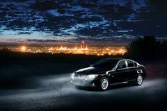 Automobile moderna nera che sta nella foresta della foschia alla notte Fotografie Stock