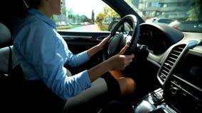 Automobile movente femminile in retromarcia, cercante il parcheggio, autista attento fotografie stock
