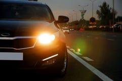 Automobile nera con il chiarore del faro immagine stock