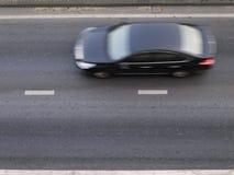 Automobile nera della sfuocatura sulla strada Immagine Stock