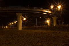 Automobile overpass with rails and night lights. Well trimmed lawn . Grass burnt places . Overpass like a giant spaceship Royalty Free Stock Photo
