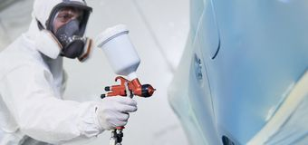 Automobile painting. car painter with gun in chamber. Painter in mask with painting gun during car automobile repair work in a paint chamber stock photos