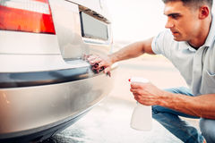 Automobile polishing on car wash station. Man rubbing vehicle bumper with polish Stock Photography