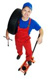 Automobile repairman with tire and lifting jack Royalty Free Stock Images