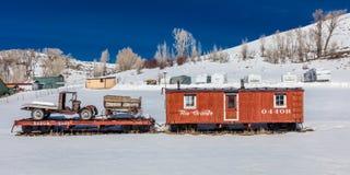 Automobile rossa antica del rarilroad e vecchi camion e vagone nel mezzo del campo nevoso in Colorado centrale nell'inverno Fotografie Stock Libere da Diritti