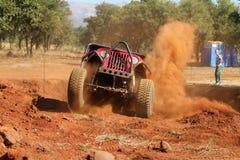 Automobile rossa che scala fuori riparo ripido che calcia sabbia e polvere Fotografia Stock