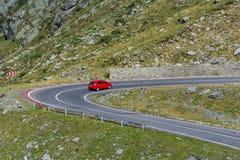 Automobile rossa sulla strada della montagna di bobina di Transfagarasn con ad elevata altitudine in montagne carpatiche Fotografie Stock