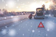 Automobile rotta su una strada nevosa di inverno fotografia stock