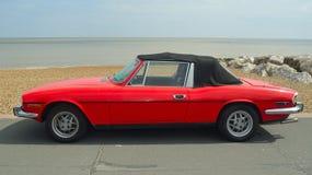 Automobile rouge classique de mâle de Triumph garée sur la promenade de bord de mer Photographie stock