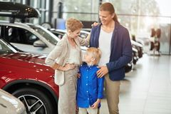 Automobile sales centre. young family with child boy in car sell royalty free stock photography
