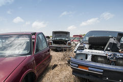 Automobile salvage yard. Junk cars in an automobile salvage yard with blue sky background Royalty Free Stock Photo