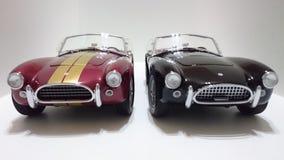 Automobile scoperta a due posti di cabrio di Shelby Cobra, bande dorate Borgogna contro le automobili nere della pittura Immagini Stock Libere da Diritti