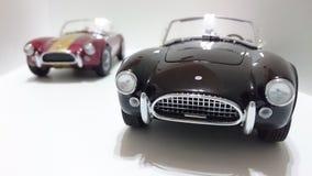Automobile scoperta a due posti di cabrio di Shelby Cobra, bande dorate Borgogna contro le automobili nere della pittura Fotografie Stock