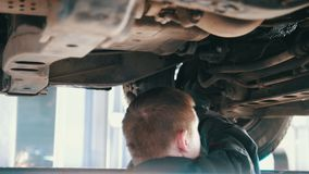 Automobile service - mechanic wrapping working device under car bottom. Slider stock video