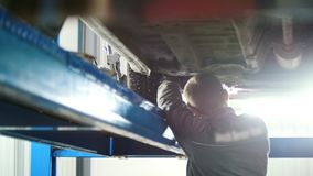 Automobile service - mechanic wrapping working device under car bottom stock video