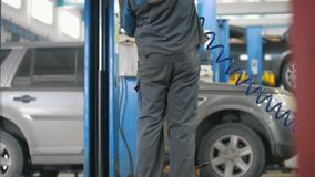 Automobile service - mechanic wrapping working device under car bottom. Slider stock footage