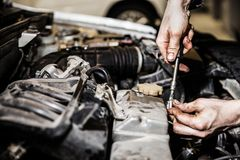 Automobile service worker or garage mechanic repairing auto car engine. Automobile service worker or garage mechanic hand holding vehicle motor maintenance tool Royalty Free Stock Photos