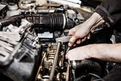 Automobile service worker or garage mechanic repairing auto car engine. Automobile service worker or garage mechanic hand holding vehicle motor maintenance tool Royalty Free Stock Image