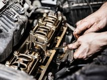 Automobile service worker or garage mechanic repairing auto car engine. Automobile service worker or garage mechanic hand holding vehicle motor maintenance tool Royalty Free Stock Photo