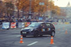 Automobile slalom and drift competitions in the city center, car on the road with cones. Kiev, Ukraine - October 22: automobile slalom and drift competitions in royalty free stock photography