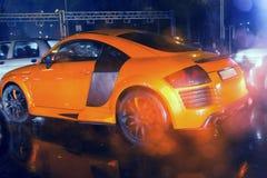 Automobile sportiva arancio aggressiva e brutale sull'immagine piovuta della strada utile per fondo Immagine Stock