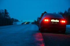 Automobile sportiva nera nella pioggia alla notte Fotografia Stock