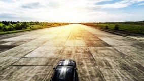 Automobile sportiva nera sulla pista abbandonata pronta a correre immagini stock