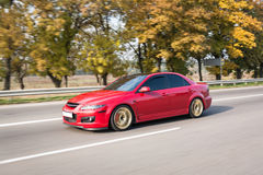 Automobile sportiva rossa sulla strada principale in autunno Immagini Stock