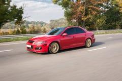 Automobile sportiva rossa sulla strada principale in autunno Immagine Stock
