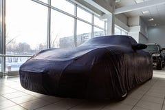 Automobile sportiva in un salone dell'automobile, per con attenzione stoccaggio di inverno, coperto di copertura professionale fa fotografia stock