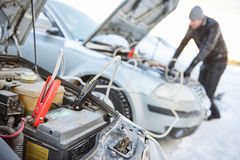 Automobile starter battery problem in winter cold weather conditions. Auto engine starting fault. Car accumulator discharged. Charging by booster jumper cables Stock Images
