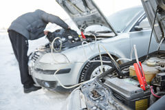 Automobile starter battery problem in winter cold weather conditions. Auto engine starting fault. Car accumulator discharged. Charging by booster jumper cables Stock Photos