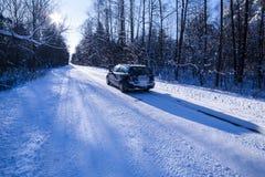 Automobile su una strada pericolosa coperta di neve e di ghiaccio. Immagine Stock