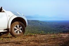 automobile 4x4 sul contesto della valle delle montagne Immagini Stock