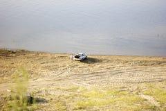 Automobile sulla spiaggia prima del lago o del mare enorme Fondo della sabbia e dell'acqua Immagine Stock Libera da Diritti