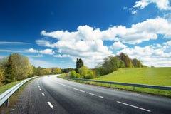 Automobile sulla strada asfaltata nel bello giorno di molla Fotografia Stock
