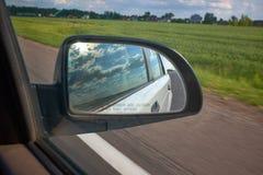 Automobile sulla strada con il fondo e lo specchietto retrovisore del mosso concetto di corsa Cielo nuvoloso fotografie stock libere da diritti