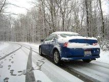 Automobile sulla strada di Snowy Immagine Stock