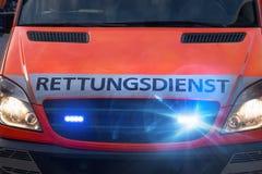 Automobile tedesca dell'ambulanza con le luci d'avvertimento infiammanti Immagine Stock
